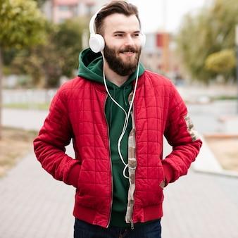 Chico sonriente de tiro medio con barba y auriculares