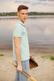 Chico sonriente de tiro medio con equipo de béisbol