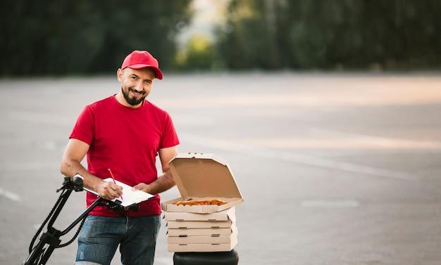 Chico sonriente de tiro medio con escritura de pizza