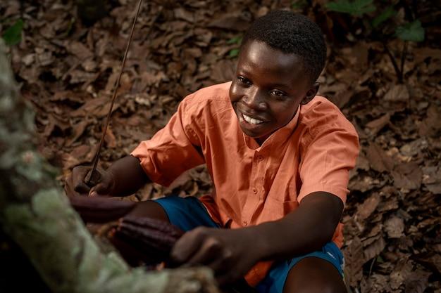 Chico sonriente de tiro medio recogiendo granos de cacao