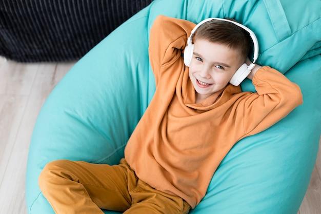 Chico sonriente de tiro medio sentado en una silla de bolsa de frijoles