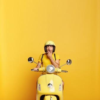 Chico sorprendido con casco conduciendo scooter amarillo