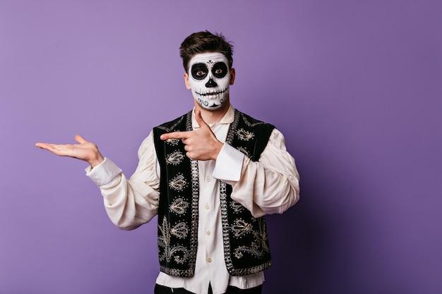 Chico sorprendido en chaleco nacional mexicano apuntando con el dedo a la izquierda. retrato de hombre con cara pintada con lugar para tex en pared lila.