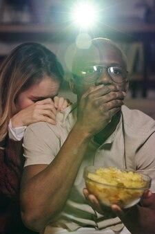 Chico sorprendido de etnia africana cubriendo la boca con la mano mientras sostiene el tazón con papas fritas, su novia molesta poniendo la cabeza en su hombro