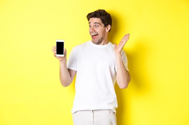 Chico sorprendido mirando la pantalla del teléfono móvil con cara de sorpresa, de pie emocionado contra la pared amarilla