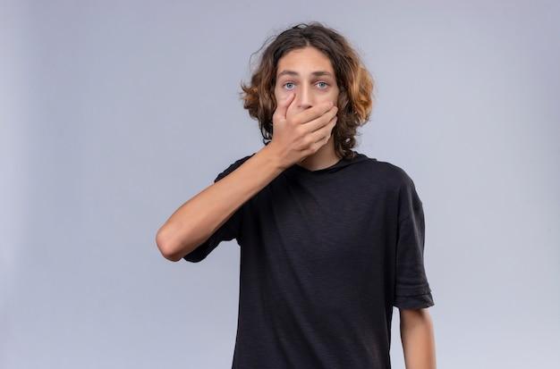 Chico sorprendido con pelo largo en camiseta negra se cubrió la boca con la mano sobre fondo blanco.