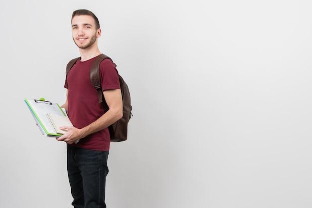 Chico sosteniendo una carpeta con notas