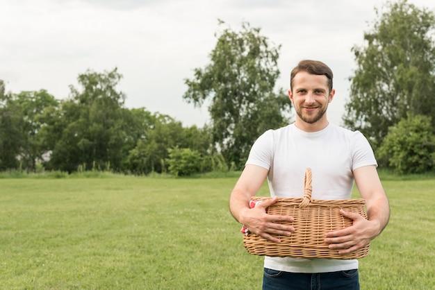 Chico sosteniendo cesta de picnic