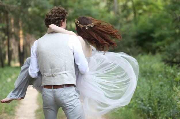 Chico sosteniendo a una chica en sus brazos y girando en el bosque
