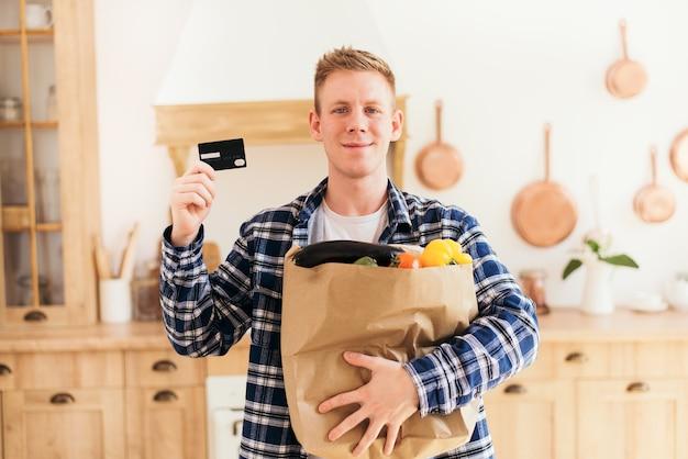 El chico sostiene un paquete de comestibles y una tarjeta de crédito en casa en la cocina, compras en línea y pago con tarjeta.
