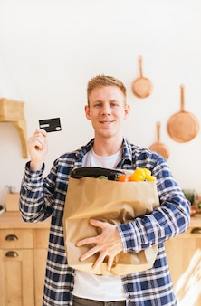 El chico sostiene un paquete de comestibles y una tarjeta de crédito en casa en la cocina de compras en línea