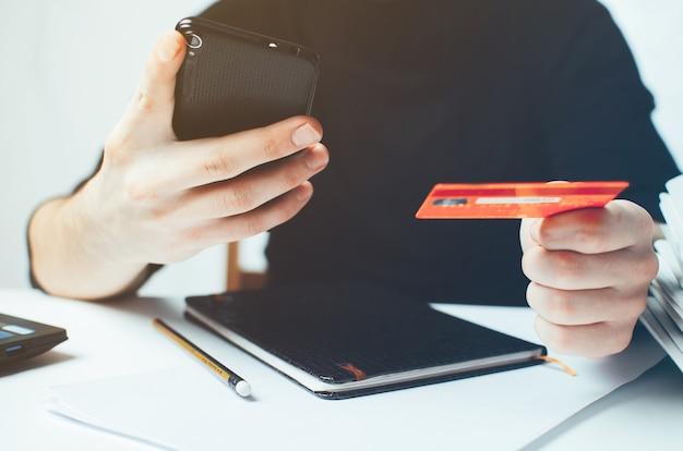El chico sostiene un teléfono y una tarjeta bancaria se recarga o paga compras