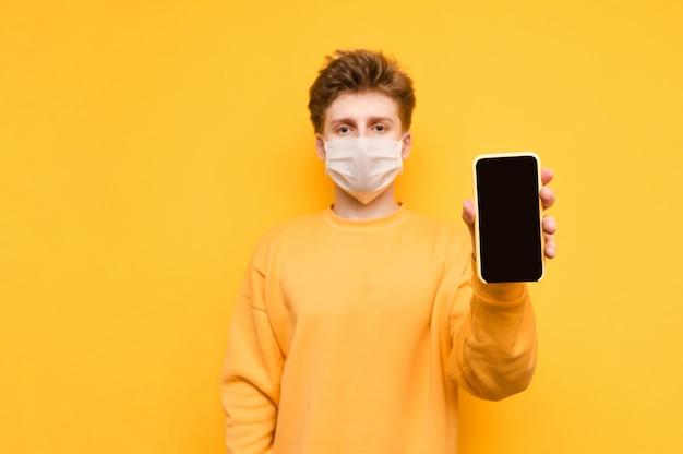 Chico con una sudadera amarilla y una máscara de gasa protectora se para sobre una naranja y le muestra a la cámara un teléfono inteligente con una pantalla negra. pandemia de coronavirus. cuarentena. covid-19.