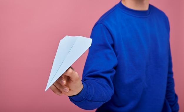 Chico de suéter azul oscuro está de pie en rosa con avión de papel azul