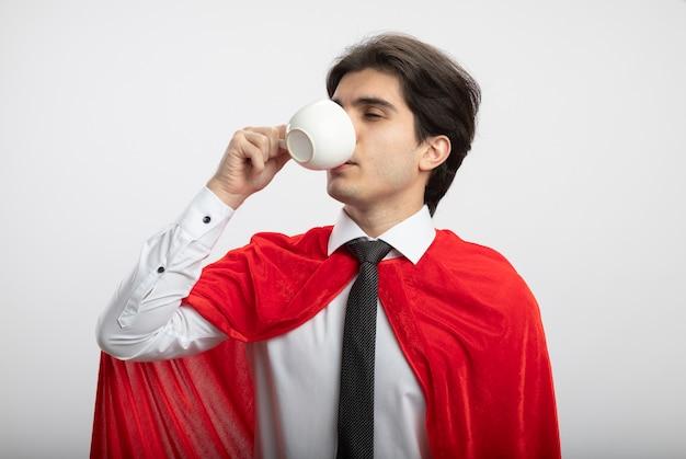 Chico superhéroe joven complacido con corbata bebe café de taza aislado sobre fondo blanco.