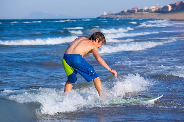 Chico surfista surfeando olas en la playa