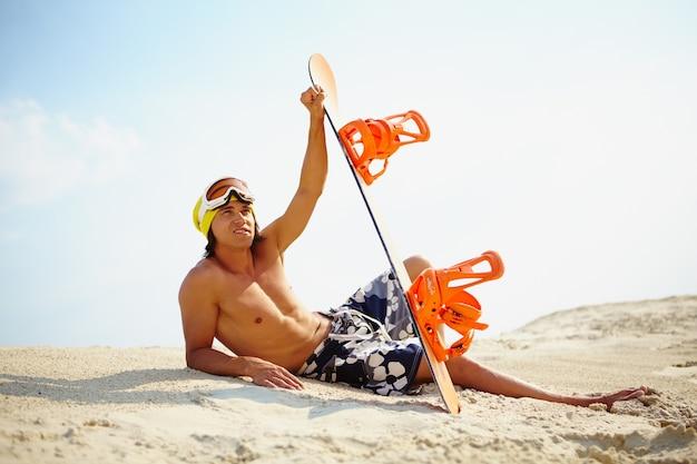 Chico con tabla de snowboard en la playa