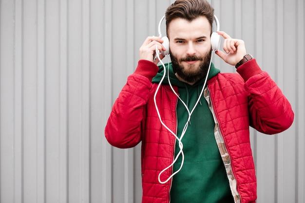 Chico de tiro medio con auriculares y chaqueta roja