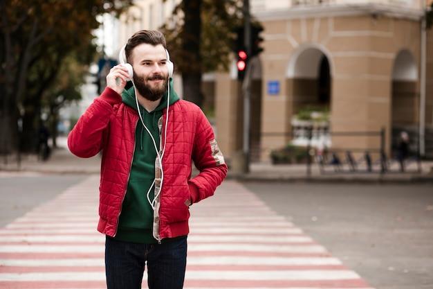 Chico de tiro medio con auriculares cruzando la calle