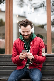 Chico de tiro medio con auriculares sentado en un banco