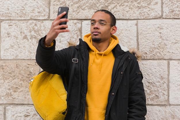 Chico de tiro medio tomando una selfie
