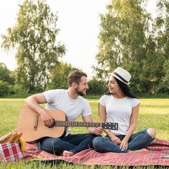 Chico tocando la guitarra a su novia sobre manta de picnic