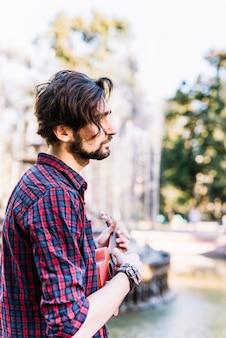 Chico tocando el ukelele junto a una fuente