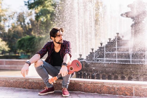 Chico tocando el ukelele sentado en una fuente