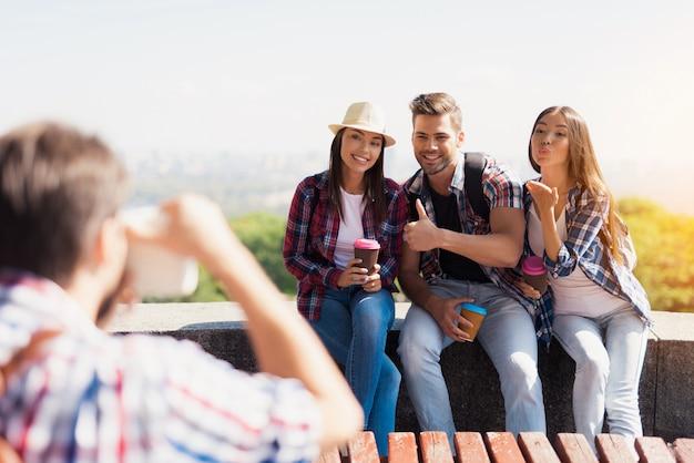 Chico toma fotos de turistas que están sentados en el parque