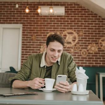 Chico tomando café en un restaurante