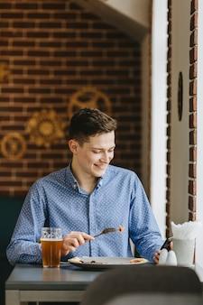 Chico tomando una cerveza en un restaurante