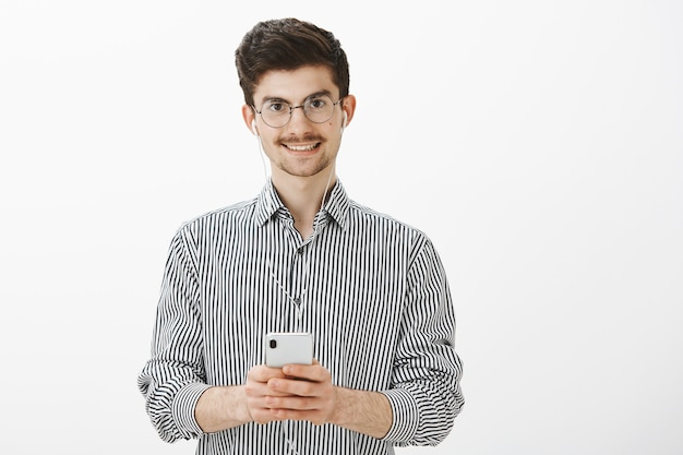 Chico tomando notas mientras escucha audiolibro. retrato de hombre caucásico atractivo amable con bigote y barba, con auriculares, disfrutando de ver un gran video en el teléfono inteligente, sonriendo