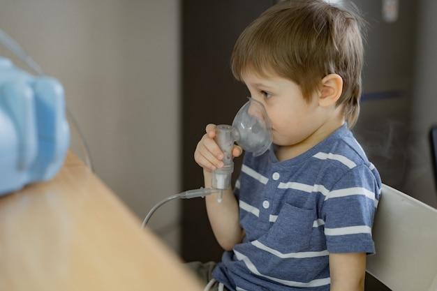 Chico tomando terapia de inhalación respiratoria con nebulizador mientras ve dibujos animados en el teléfono