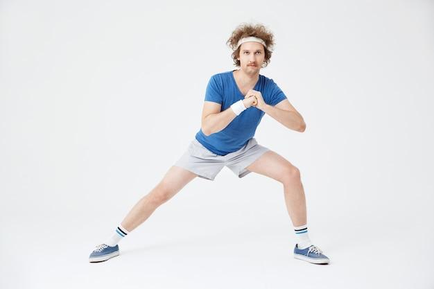Chico en traje deportivo retro haciendo ejercicios de estiramiento. blanco