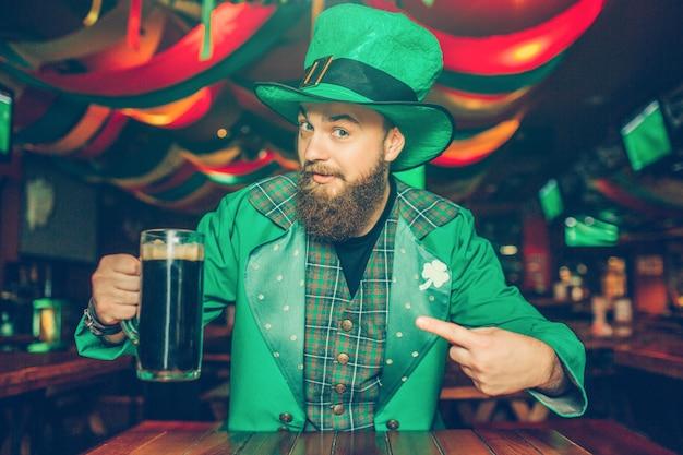 Chico en traje verde sentarse a la mesa en el pub y posando. sostiene una jarra de cerveza oscura y mira. el es confidente.