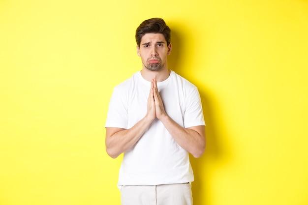 Chico triste pidiendo algo, enfurruñado y pidiendo un favor, pidiendo perdón, de pie sobre un fondo amarillo.