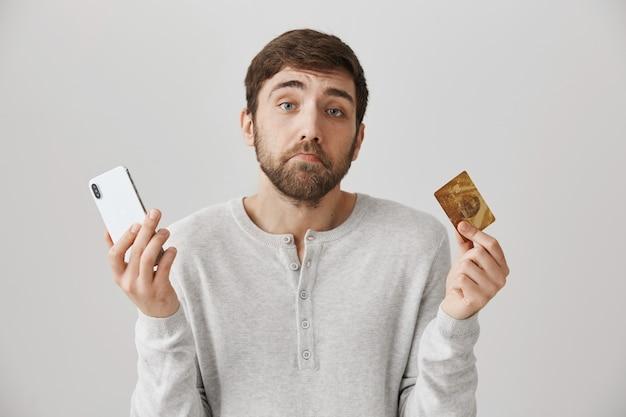 Chico triste triste encogiéndose de hombros, sosteniendo la tarjeta de crédito y el teléfono móvil
