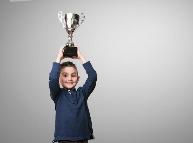 Chico con un trofeo encima de su cabeza