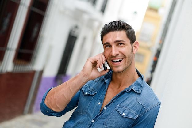 Chico usando su móvil con una gran sonrisa Foto gratis