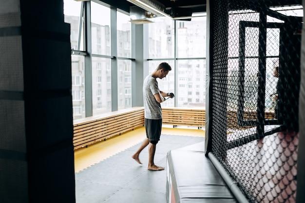 Chico vestido con la camiseta gris envuelve un vendaje en la mano en el gimnasio de boxeo con el telón de fondo de las ventanas panorámicas.