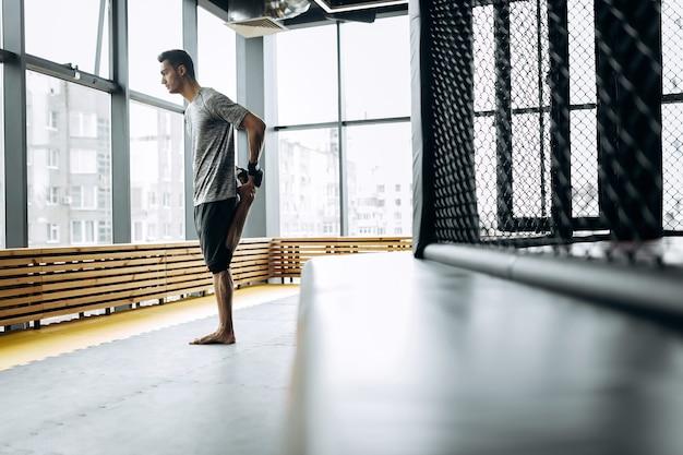 Chico vestido con la camiseta gris estira los brazos en el gimnasio de boxeo con ventanas panorámicas.
