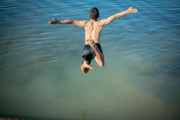 Chicos activos saltando de troncos en el agua.