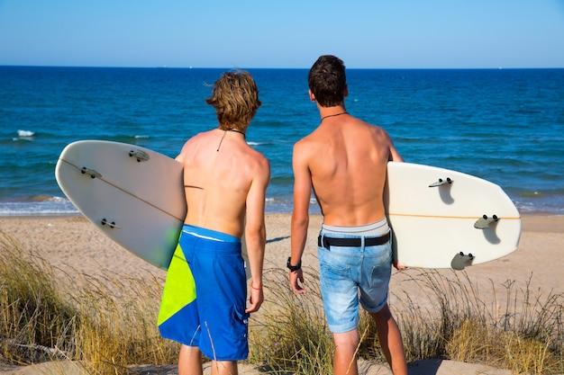Chicos adolescentes surfistas vista trasera mirando a la playa