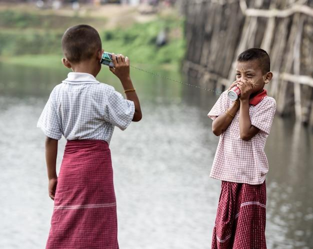 Chicos asiáticos hablando por un teléfono de latas