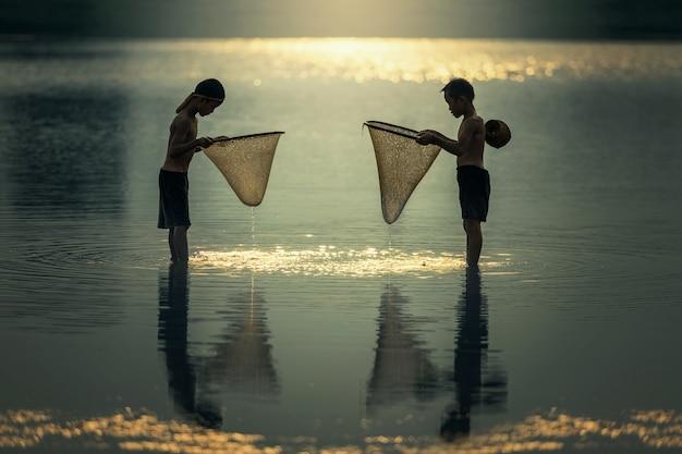 Chicos asiáticos pescando en el río