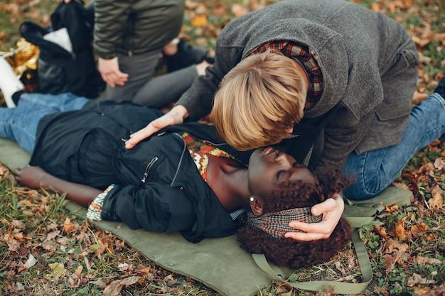 Los chicos ayudan a una mujer. niña africana yace inconsciente. brindar primeros auxilios en el parque.