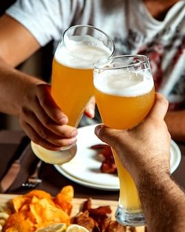 Chicos bebiendo cerveza con aperitivos mixtos