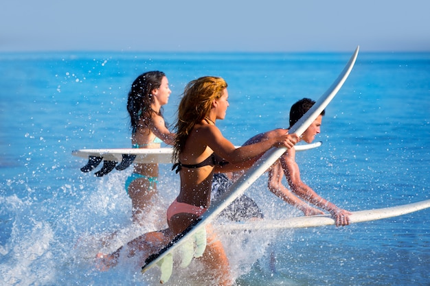 Chicos y chicas adolescentes surfistas corriendo saltando en la playa.