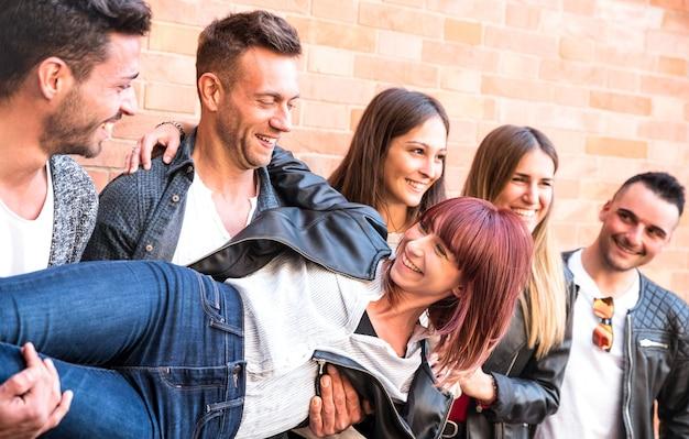 Chicos y chicas multiculturales milenarios sosteniendo a una amiga y divirtiéndose genuinamente