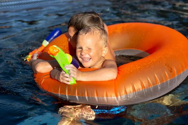 Chicos divirtiéndose en la piscina con flotador y pistola de agua.